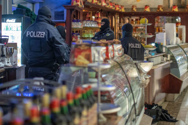 Masked police stand in an ice parlor in Duisburg, western Germany, Wednesday, Dec. 5, 2018 as authorities conduct coordinated raids in Germany, Italy, Belgium and the Netherlands in a crackdown on the Italian mafia.